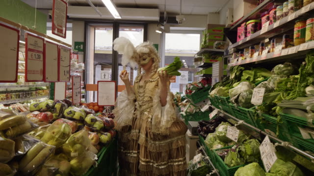 woman wearing historical clothing and carnival mask shopping for vegetables in grocery store - historical clothing stock videos & royalty-free footage