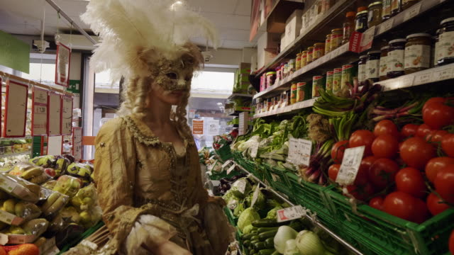 woman wearing historical clothing and carnival mask shopping for tomatoes in grocery store - fasching stock-videos und b-roll-filmmaterial