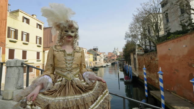 woman wearing historical clothing and carnival mask standing on bridge over canal - historical clothing stock videos & royalty-free footage
