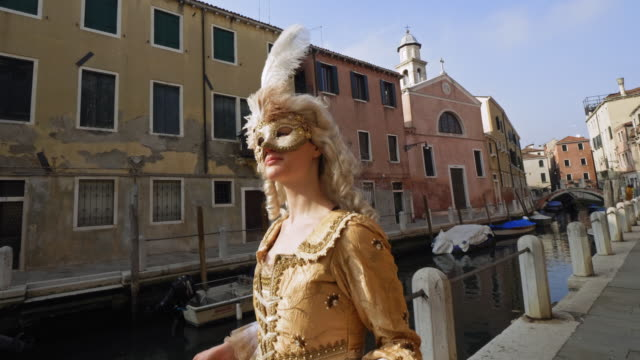 woman wearing historical clothing and carnival mask walking by canal - historical clothing stock videos & royalty-free footage