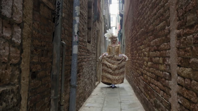 woman wearing historical clothing and carnival mask walking in narrow alley - historical clothing stock videos & royalty-free footage