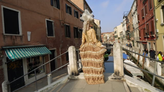 woman wearing historical clothing and carnival mask walking on bridge over canal - historical clothing stock videos & royalty-free footage