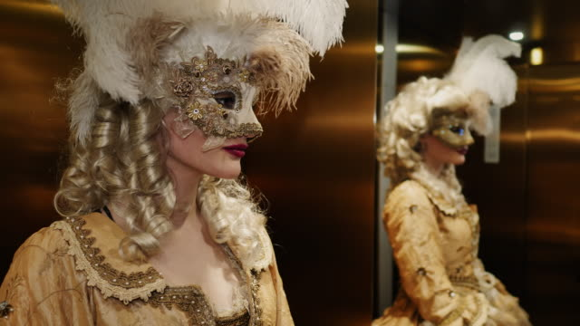 woman wearing historical clothing and venetian mask standing in front of mirror in elevator - mirror stock videos & royalty-free footage
