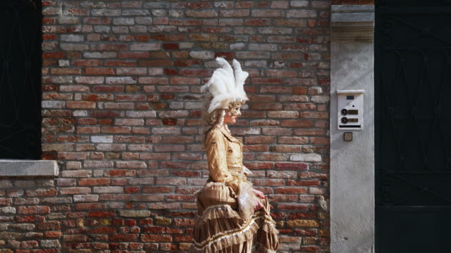 woman wearing historical clothing and venetian mask walking alongside brick building - historical clothing stock videos & royalty-free footage