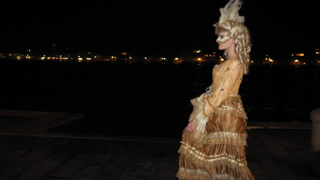 woman wearing historical clothing and venetian mask walking on promenade at night - lagoon stock videos & royalty-free footage