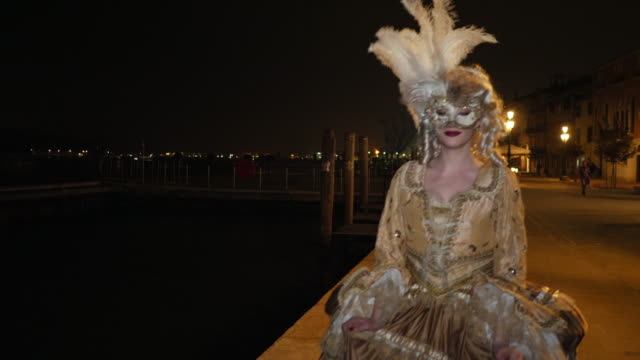 woman wearing historical clothing and venetian mask walking on promenade at night - historical clothing stock videos & royalty-free footage