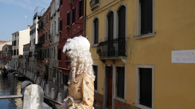woman wearing historical clothing and venetian mask walking on footbridge over canal - historical clothing stock videos & royalty-free footage