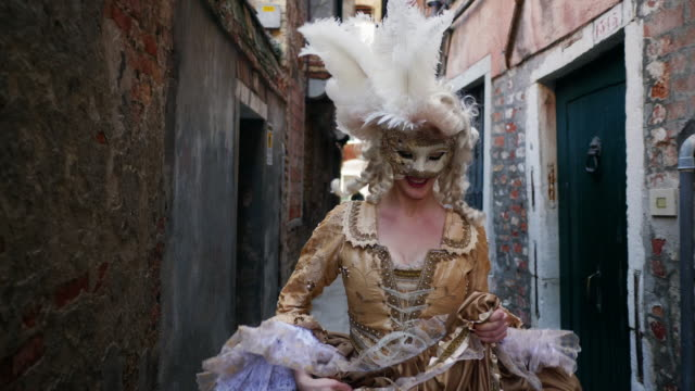 woman wearing historical clothing walking in narrow alley - allegro video stock e b–roll