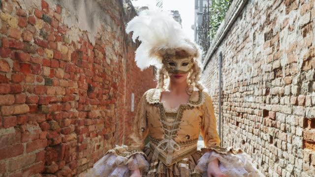 woman wearing historical clothing walking in narrow alley - kamerafahrt auf schienen stock-videos und b-roll-filmmaterial