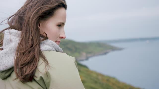 Woman wearing hoodie looking over landscape
