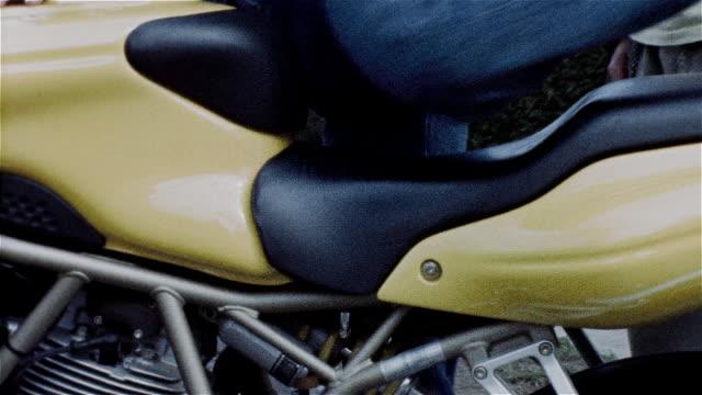 vidéos et rushes de woman wearing jeans getting on motorcycle - procédé croisé