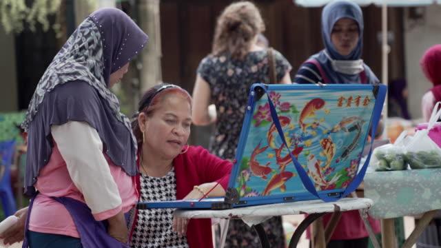 woman wearing khimaar looking a vendor lottery tickets - strategia di vendita video stock e b–roll
