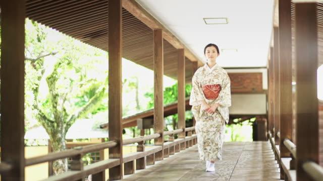 vídeos y material grabado en eventos de stock de woman wearing kimono walks towards camera - templo
