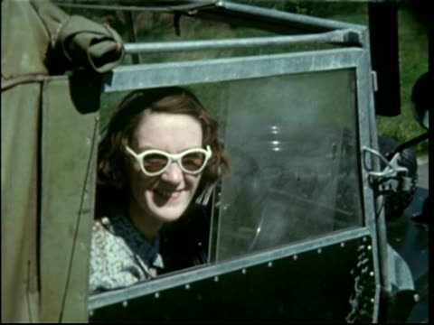 Woman wearing large sunglasses, in landrover, 1950s
