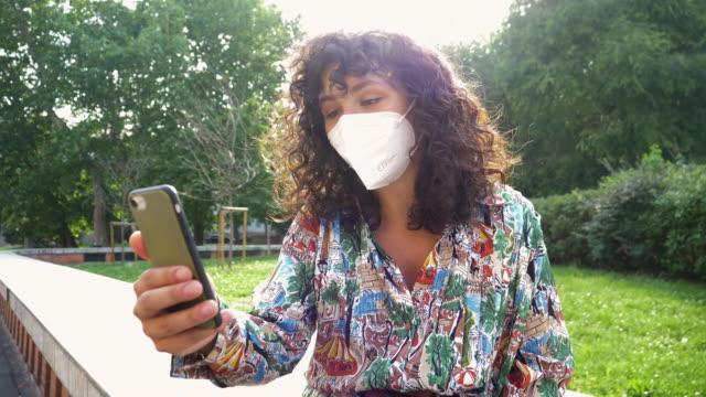 woman wearing mask having video call - endast unga kvinnor bildbanksvideor och videomaterial från bakom kulisserna