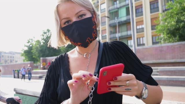 woman wearing mask using smart phone - medium length hair stock videos & royalty-free footage