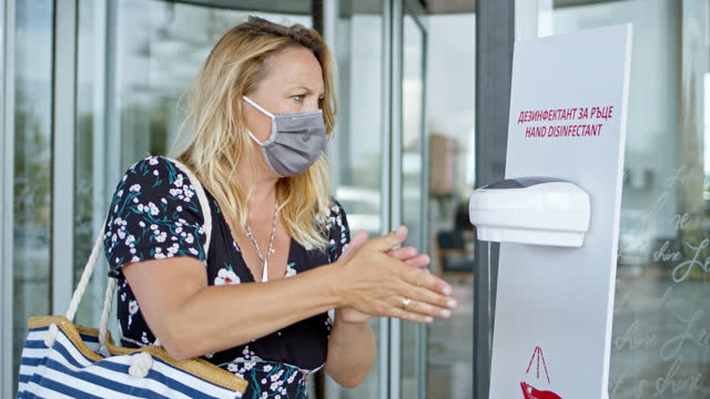 woman wearing mouth nose protection mask and summer dress uses hand disinfectant while leaving hotel building - one mature woman only stock videos & royalty-free footage