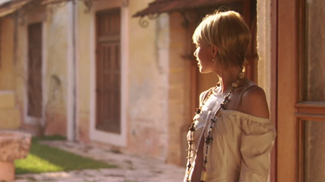 vídeos y material grabado en eventos de stock de ms woman wearing off-the-shoulder blouse and standing in doorway at hacienda xcanatun / merida, mexico  - collar