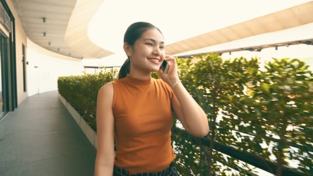 Woman wearing orange dress and call mobile phone happily