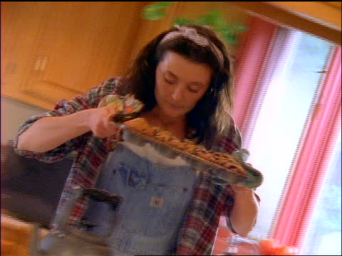 woman wearing overalls in kitchen taking muffins out of oven + tests them with toothpick - muffin stock videos and b-roll footage