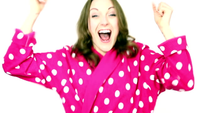stockvideo's en b-roll-footage met woman wearing pink spotted bathrobe dressing gown cheering and celebrating. - badjas
