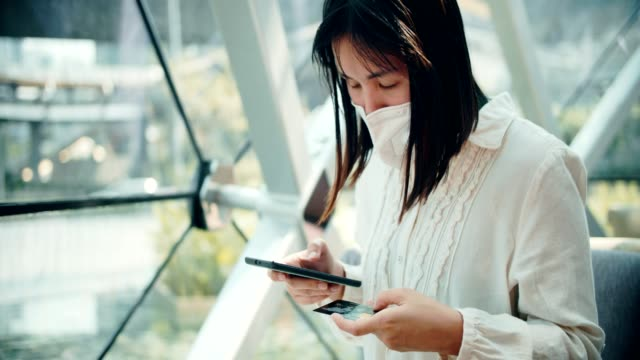 woman wearing pollution mask is shopping online with smartphone - pollution mask stock videos and b-roll footage