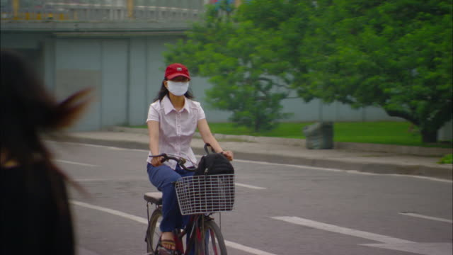 ms pan woman wearing pollution mask riding bike down street, beijing, beijing, china - protective mask workwear stock videos and b-roll footage