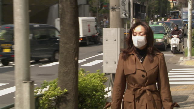 vídeos de stock e filmes b-roll de ms zo woman wearing pollution mask walking along street, tokyo, japan - máscara de proteção