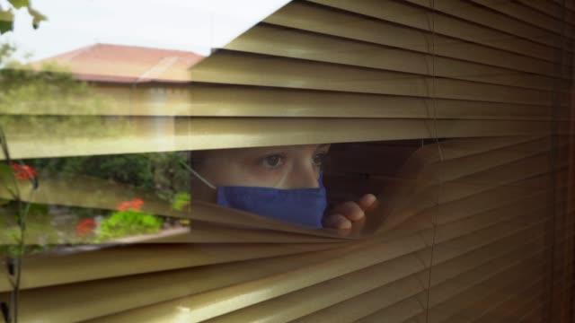 stockvideo's en b-roll-footage met vrouw die prorective gezichtsmasker tijdens covid-19 pandemie draagt - gluren