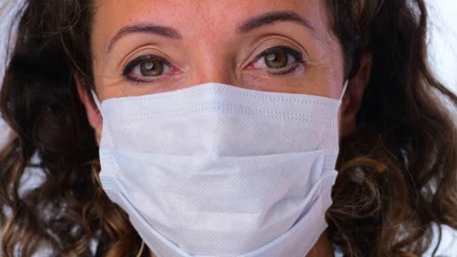 保護フェイスマスクを着用し、笑顔の女性 - 使い捨て製品点の映像素材/bロール