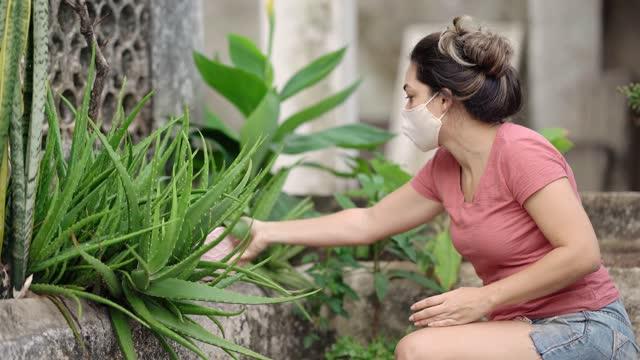 frau trägt schutzmaske, die pflanzen kultiviert - 30 34 years stock-videos und b-roll-filmmaterial