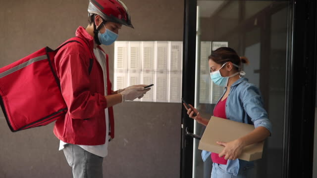 vídeos de stock e filmes b-roll de woman wearing protective mask taking pizza from delivery person during coronavirus pandemic - pagar