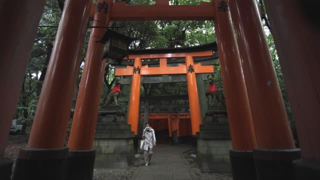 ws woman wearing protective mask walking under torii gates leading to inner fushimi inari taisha shrine, kyoto, japan - 石材点の映像素材/bロール
