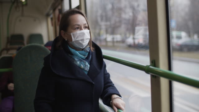 vídeos de stock e filmes b-roll de woman wearing protective medical mask in bus - transportation
