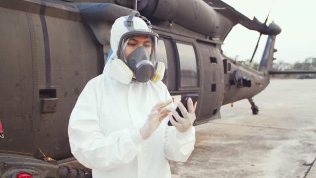 frau trägt schutzanzüge und mit smartphone. - army soldier stock-videos und b-roll-filmmaterial