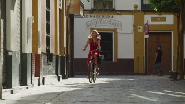 woman wearing red dress riding bicycle on cobblestone street / seville, sevilla, spain - dress stock videos & royalty-free footage