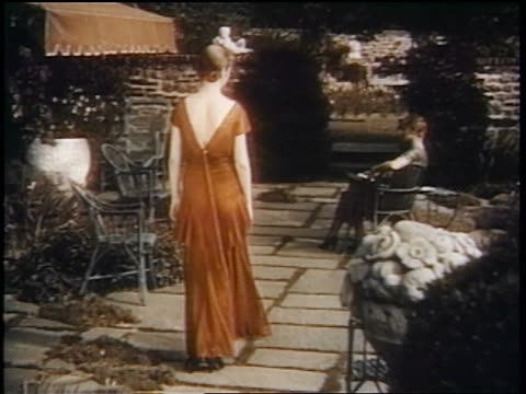 stockvideo's en b-roll-footage met 1938 rear view woman wearing red dress walking toward woman sitting in garden - 1938