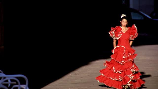 woman wearing red flamenco dress walking on sidewalk toward camera / madrid, spain - flamenco danza tradizionale video stock e b–roll