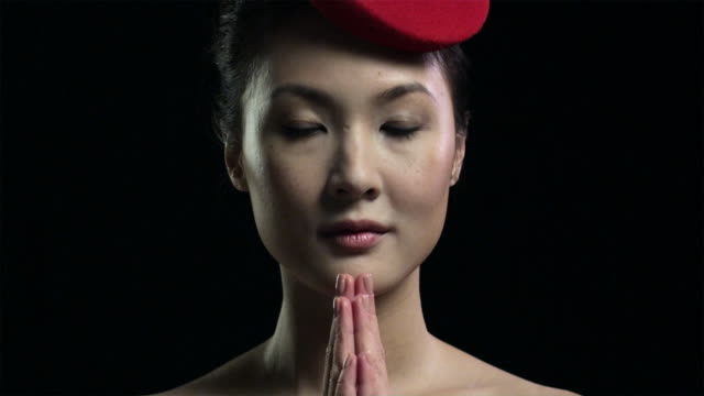 vidéos et rushes de woman wearing red hat with hands together - respect