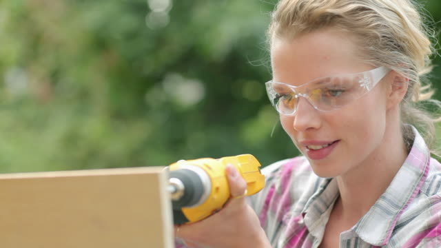 Woman wearing safety goggles drilling plywood with electric drill