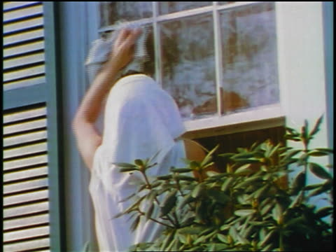 1957 rear view woman wearing scarf on head washing window of house - 1957 stock-videos und b-roll-filmmaterial