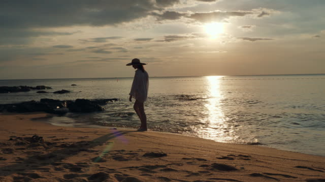 vídeos y material grabado en eventos de stock de woman wearing shirt and hat walking on beach at sunset - accesorio de cabeza