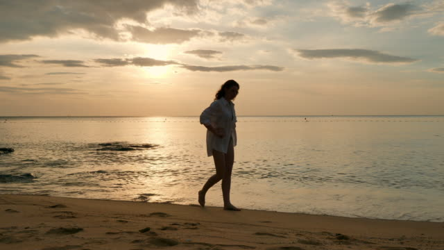 vídeos de stock e filmes b-roll de woman wearing shirt walking on beach at sunset - vietname
