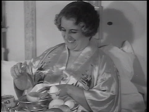 B/W 1934 woman wearing silk pajamas in bed eating grapefruit from breakfast tray / cruise ship