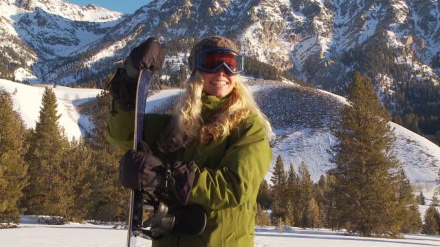 vídeos de stock e filmes b-roll de woman wearing snow gear poses with snowboard / blaine county, idaho, united states - roupa de esqui