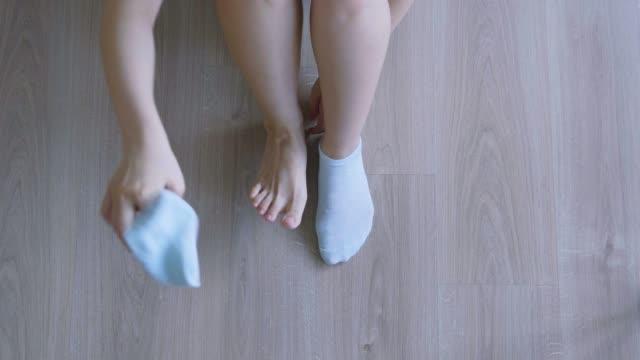 vídeos y material grabado en eventos de stock de mujer vistiendo calcetines en el suelo - malos olores