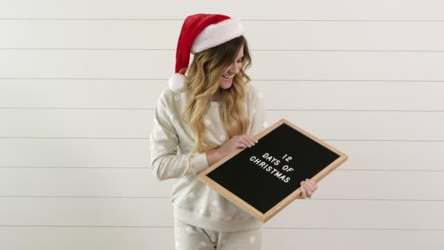 woman wearing stocking cap looks at sign she is holding saying, 12 days of christmas - weihnachtsmütze stock-videos und b-roll-filmmaterial