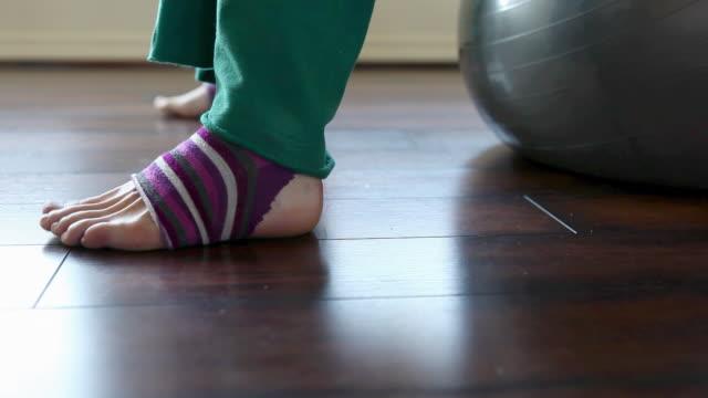 woman wearing striped leg warmers on pilates ball - leg warmers stock videos & royalty-free footage