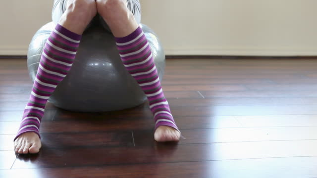 woman wearing striped leg warmers on pilates ball - fitness ball stock videos & royalty-free footage