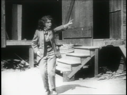 B/W 1914 woman (Minta Durfee) wearing suit talking to herself + pointing at something offscreen